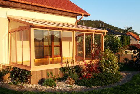 Hlinková zimna záhrada s bezpečnostným sklom na streche, bezpečnostným sklom ako výplň rámových posuvov a drevenou podlahou.